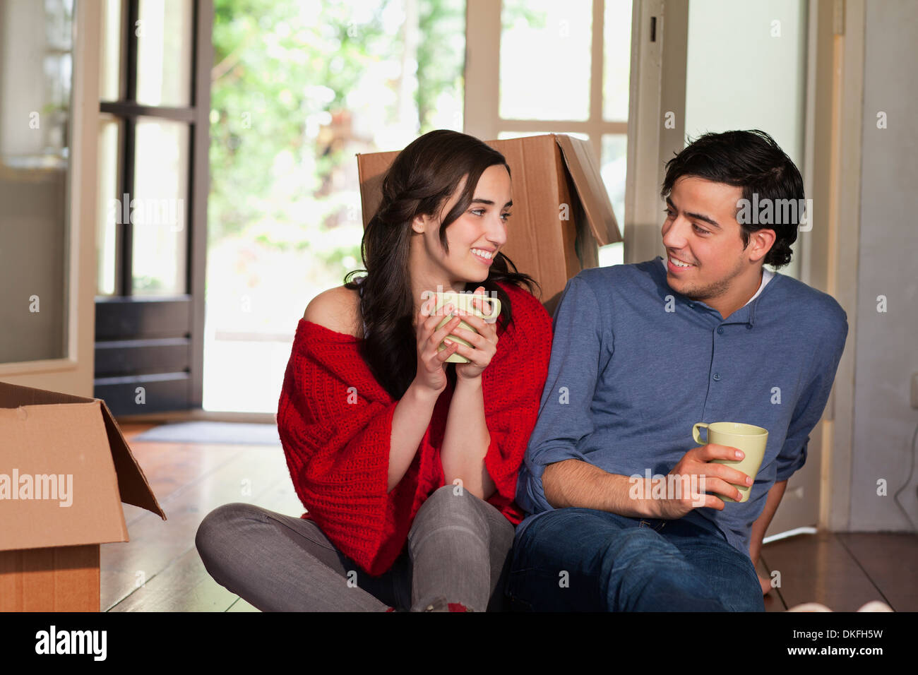 Young couple having coffee break whilst moving house - Stock Image