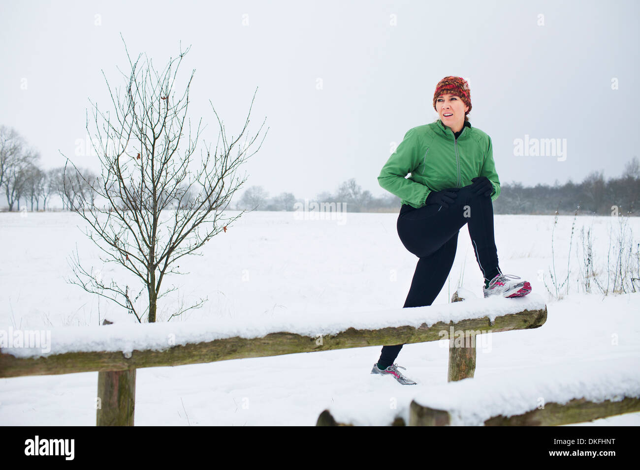 Female jogger stretching before run in snow covered scene - Stock Image