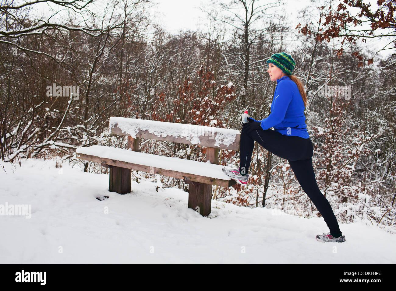 Female runner doing stretch exercises in snow - Stock Image