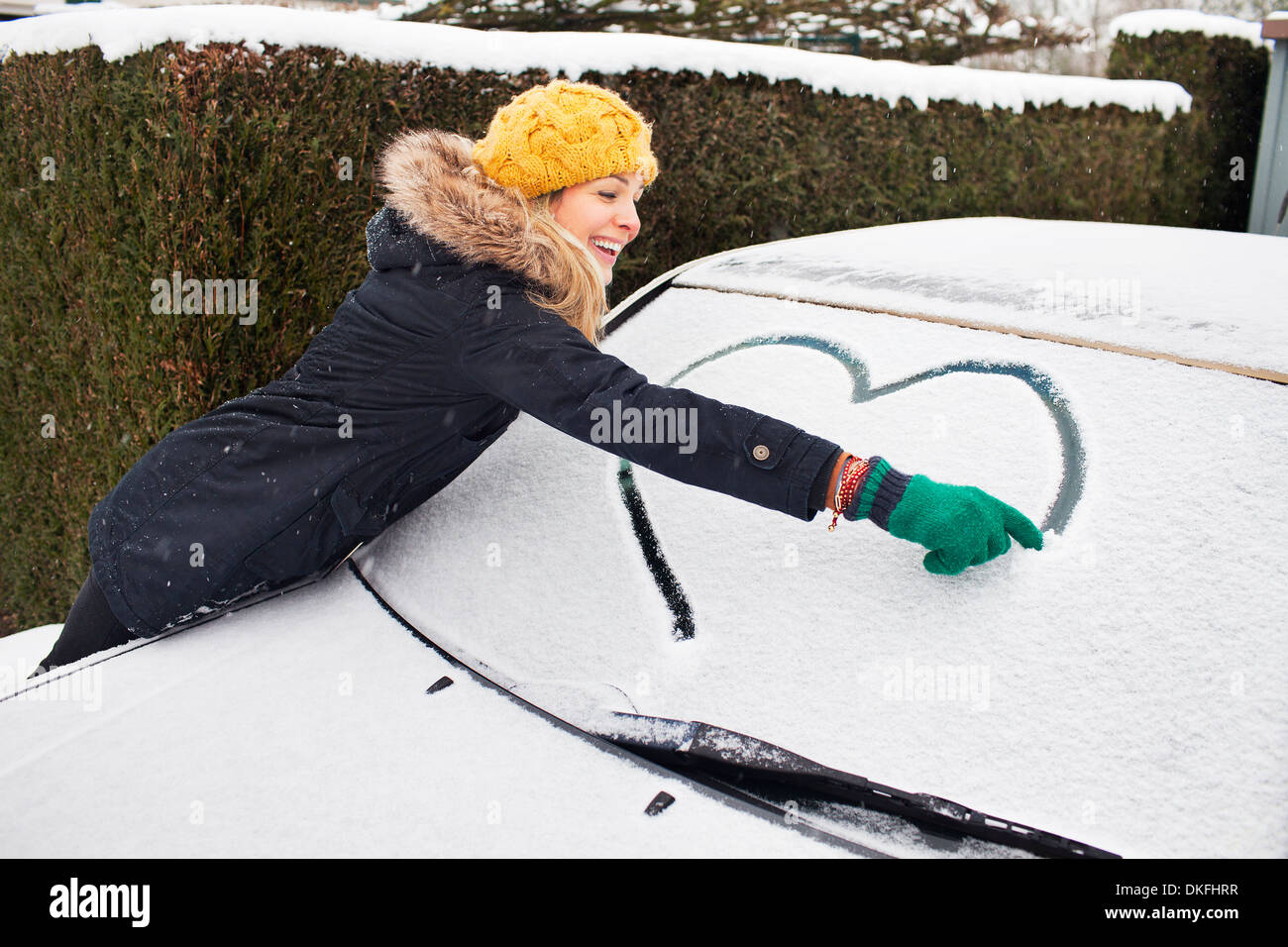 Woman drawing heart shape on snow covered windscreen - Stock Image