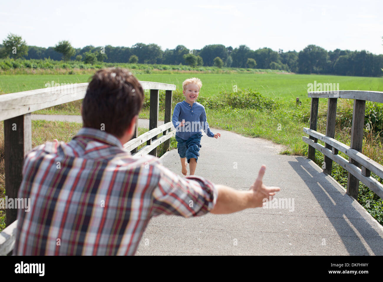 Boy running over wooden bridge towards dad - Stock Image