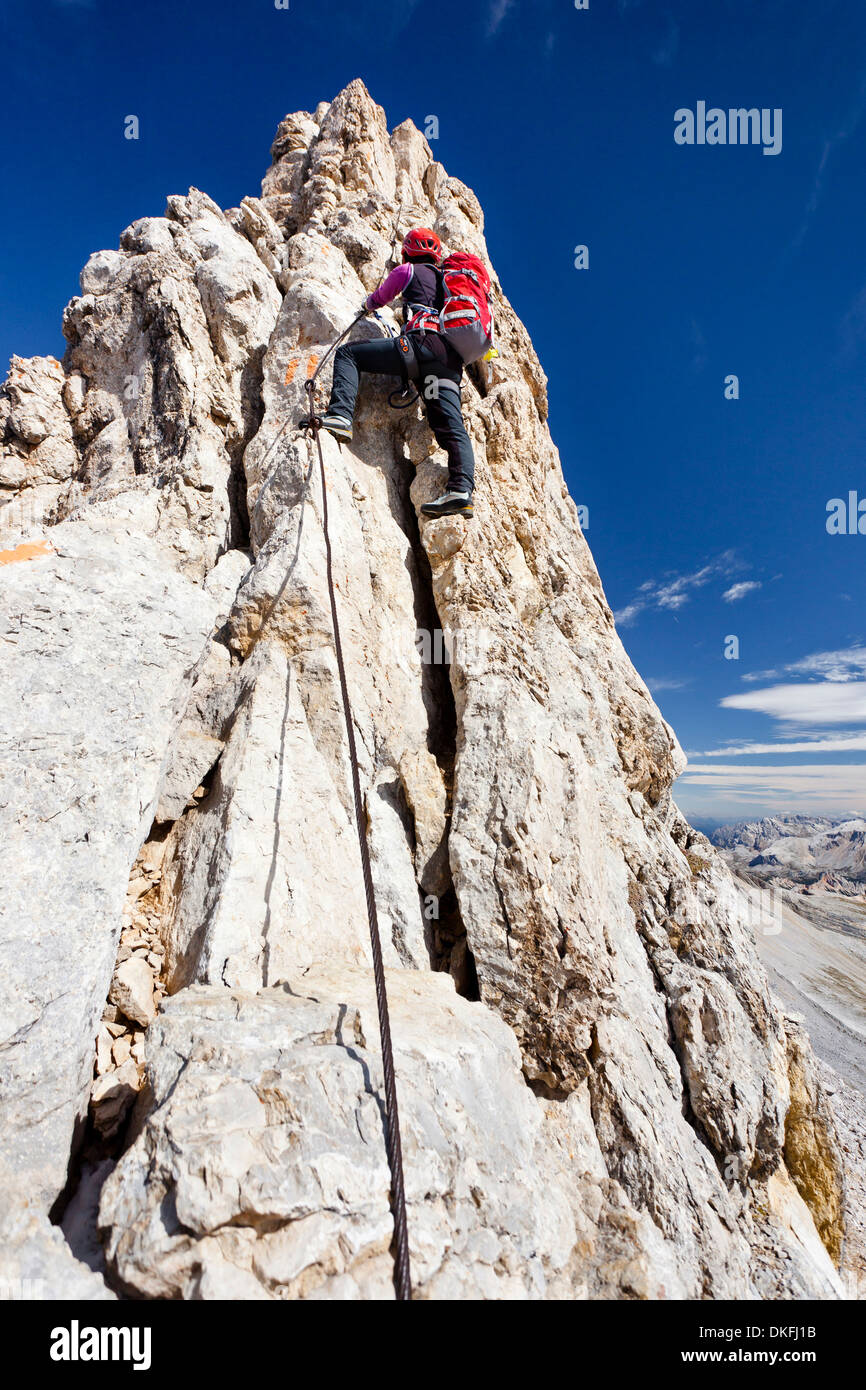 Mountain climber ascending along the Zehner Ferrata climbing route to Zehnerspitze Mountain in the Fanes Group in - Stock Image