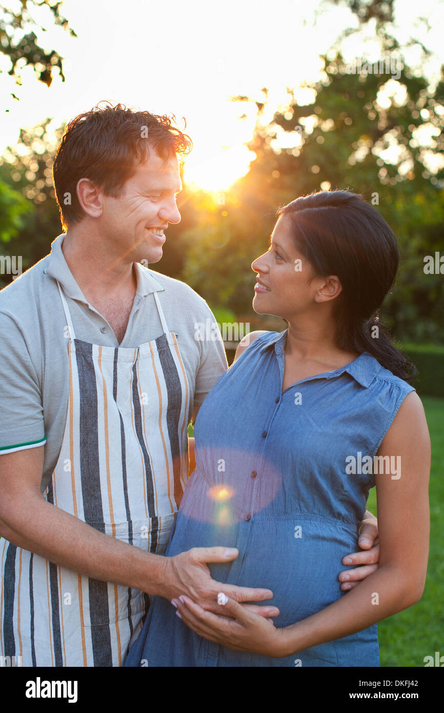 Man hugging pregnant woman, hands on stomach - Stock Image