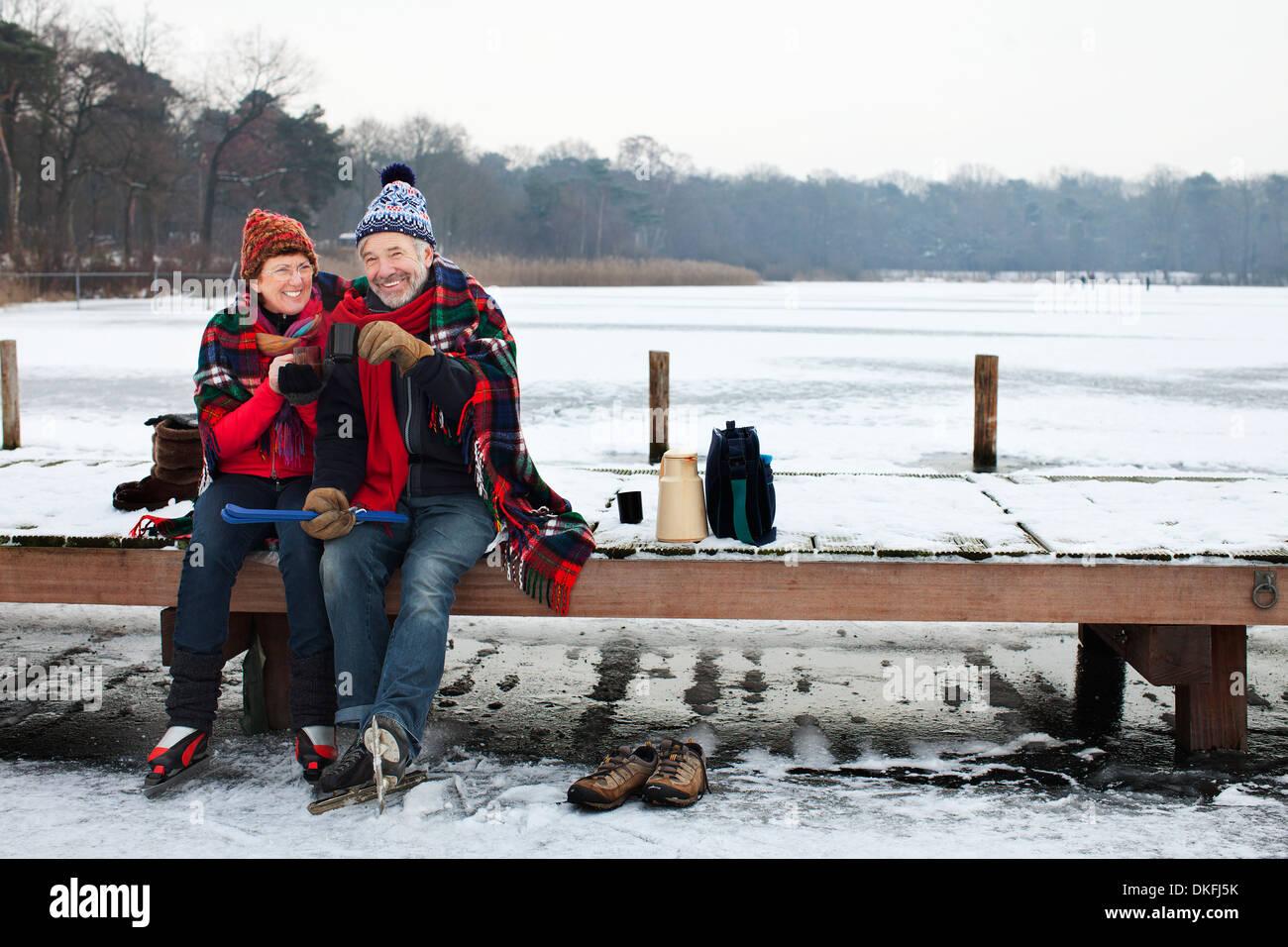 Couple sitting on pier having hot drink - Stock Image