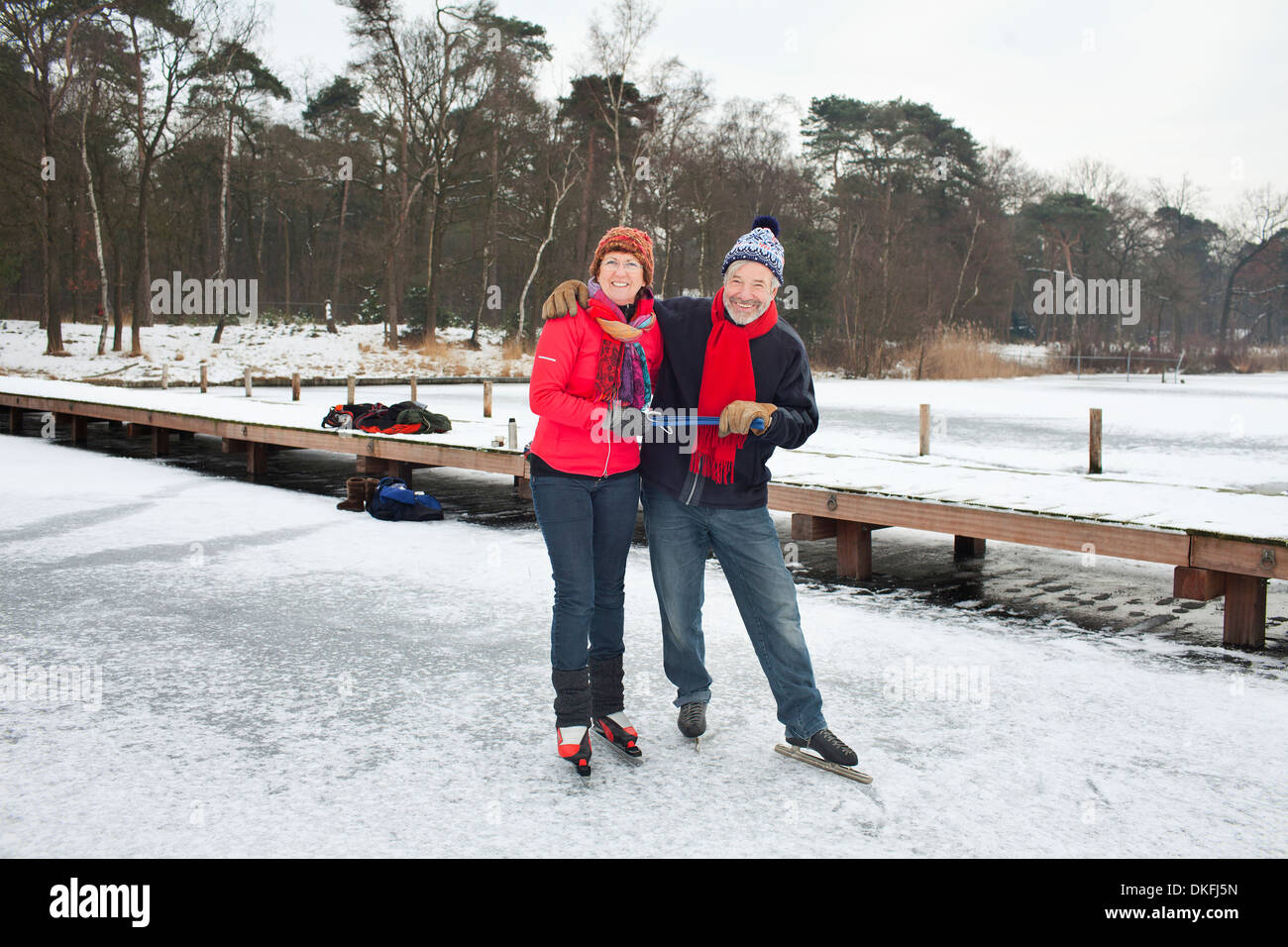 Couple ice skating, holding hands - Stock Image