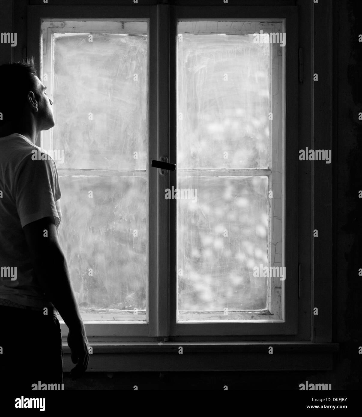 Man standing at window - Stock Image