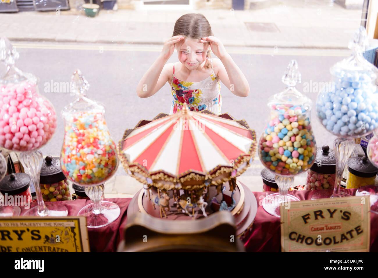 Girl looking through window of sweet shop Stock Photo