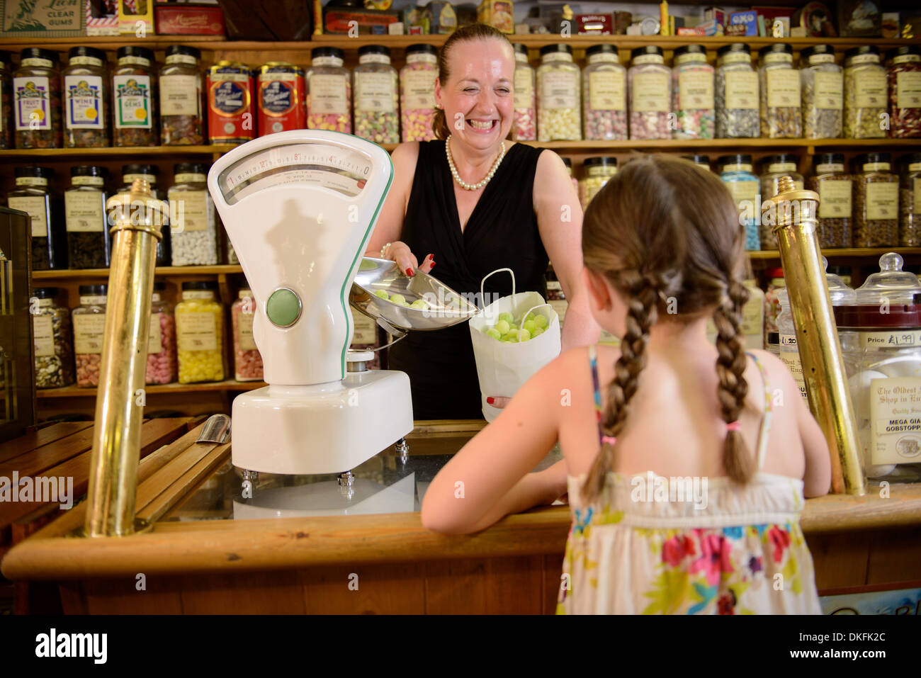 Girl buying bag of sweets from traditional sweet shop - Stock Image