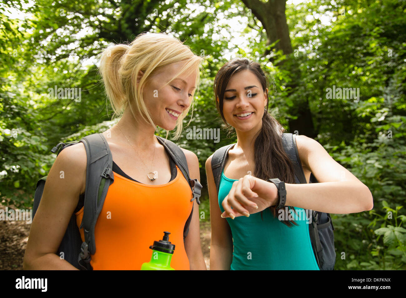 Women out walking in forest, checking the time - Stock Image