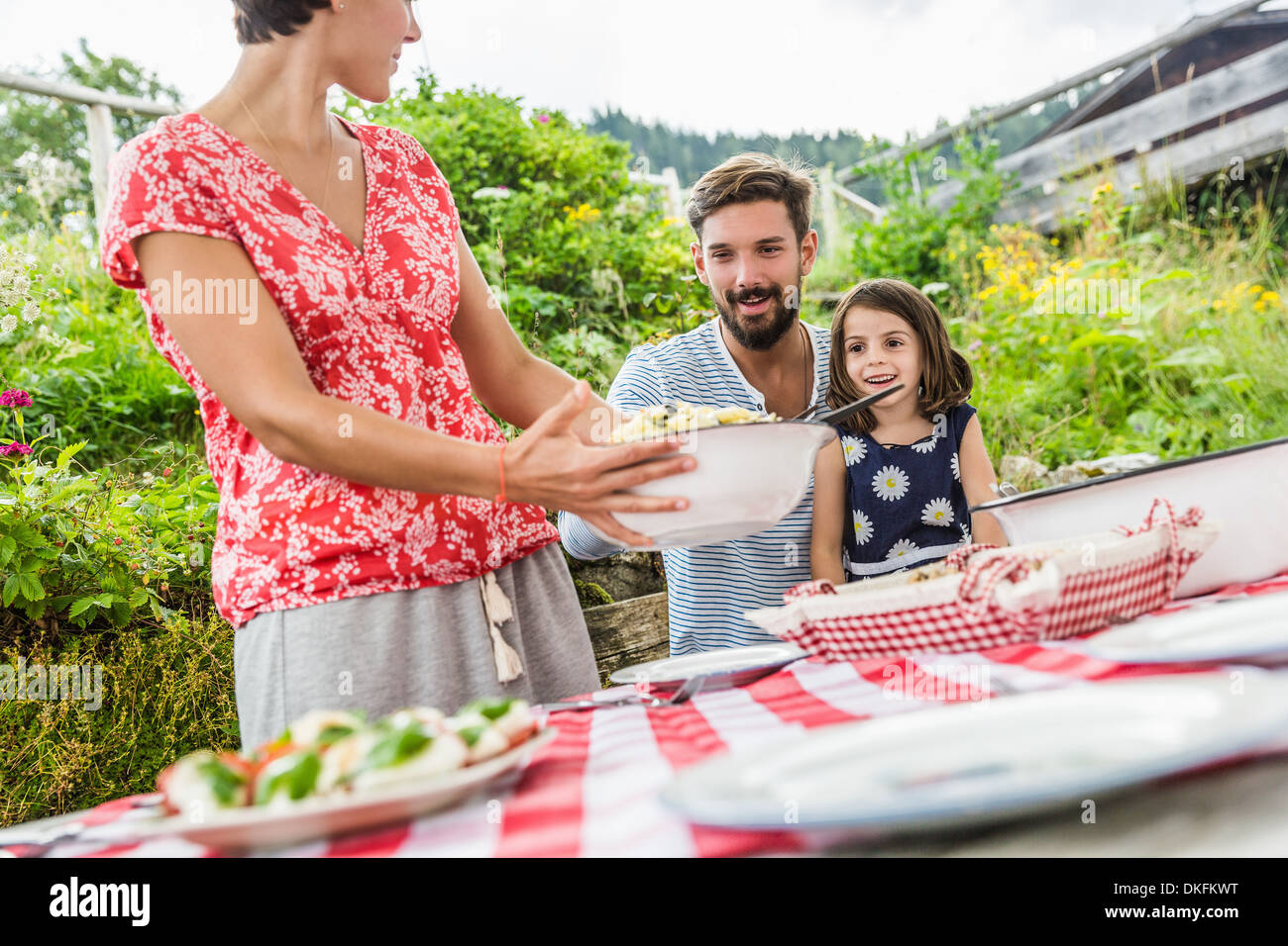 Young family sharing picnic lunch, Tyrol, Austria - Stock Image