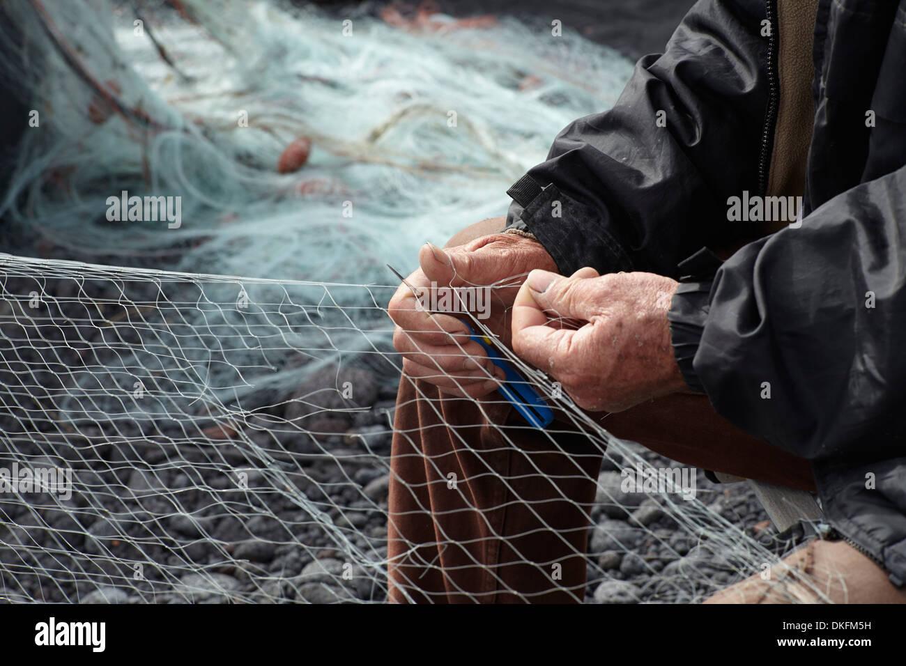 Fisherman repairing net on pebble beach - Stock Image