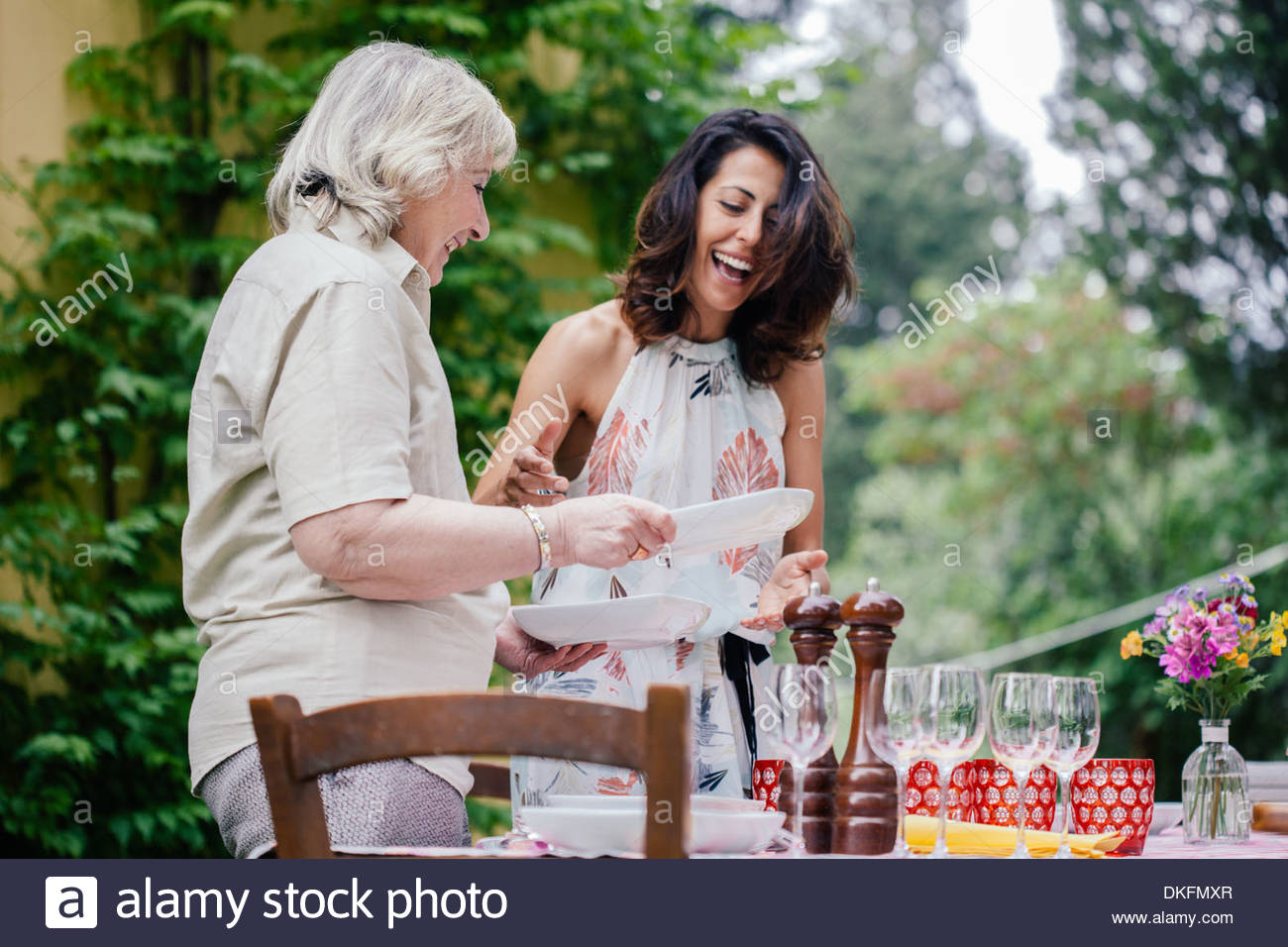 Mother and adult daughter setting table for family meal - Stock Image
