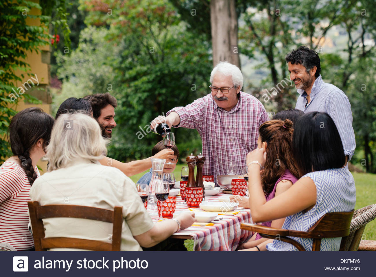 Senior man pouring wine at family meal - Stock Image