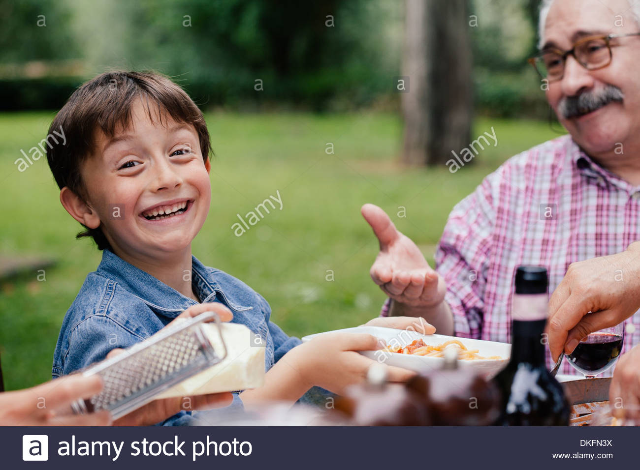 Happy boy and grandfather at family meal - Stock Image