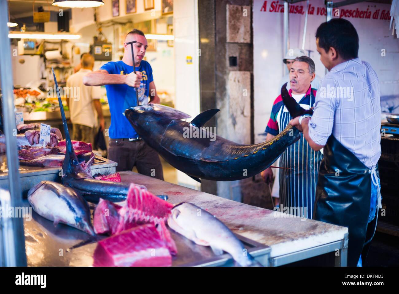 Fishmonger about to fillet an enormous tuna at Syracuse Market on Ortigia Island, Syracuse, Sicily, Italy, Europe - Stock Image
