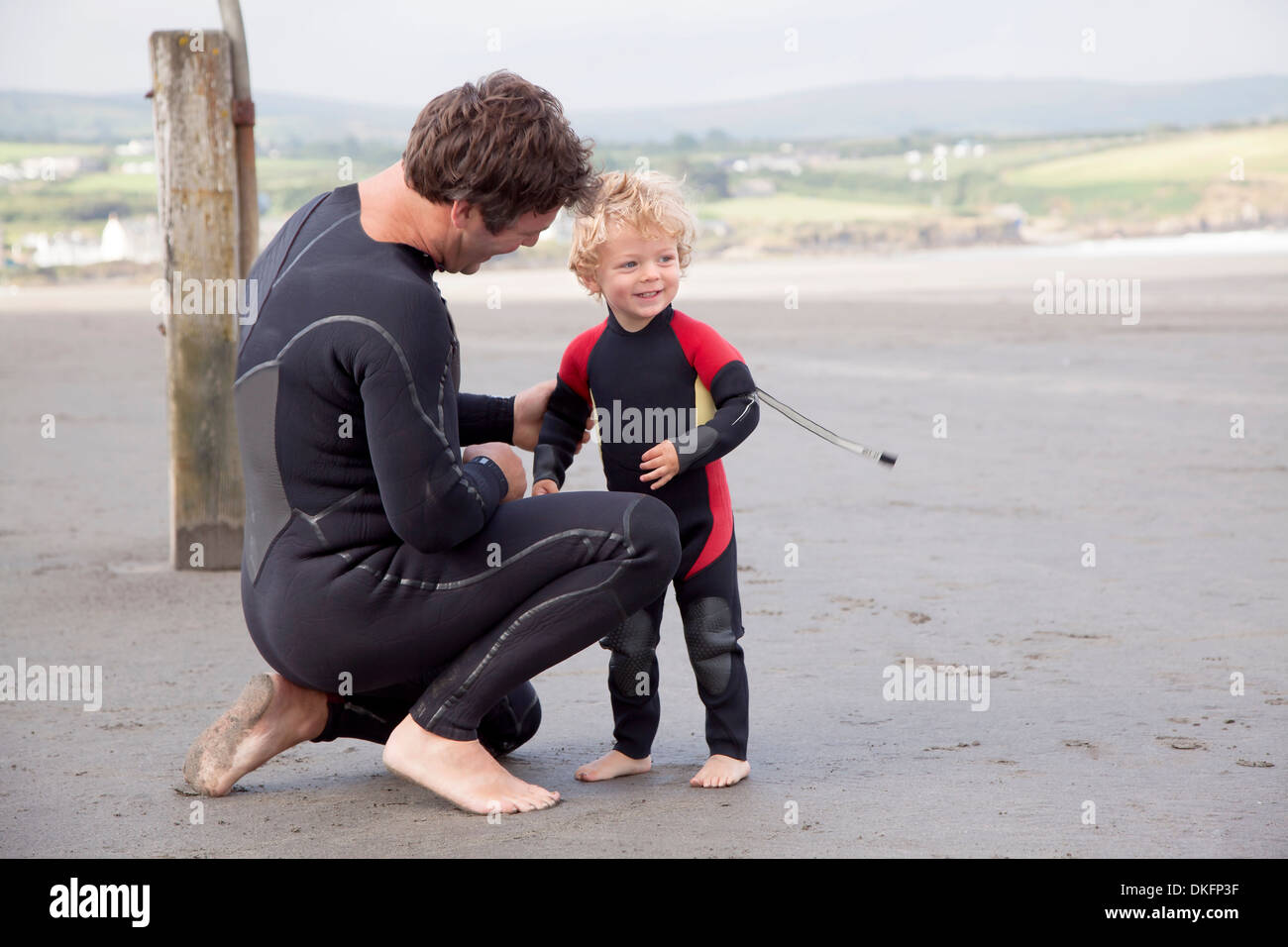 Father and son on beach wearing wet suits - Stock Image