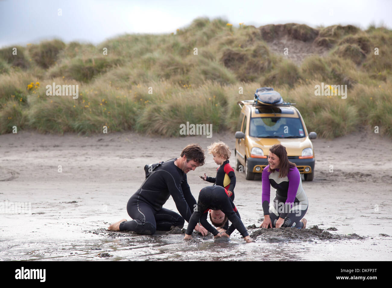 Family with two boys playing on beach - Stock Image