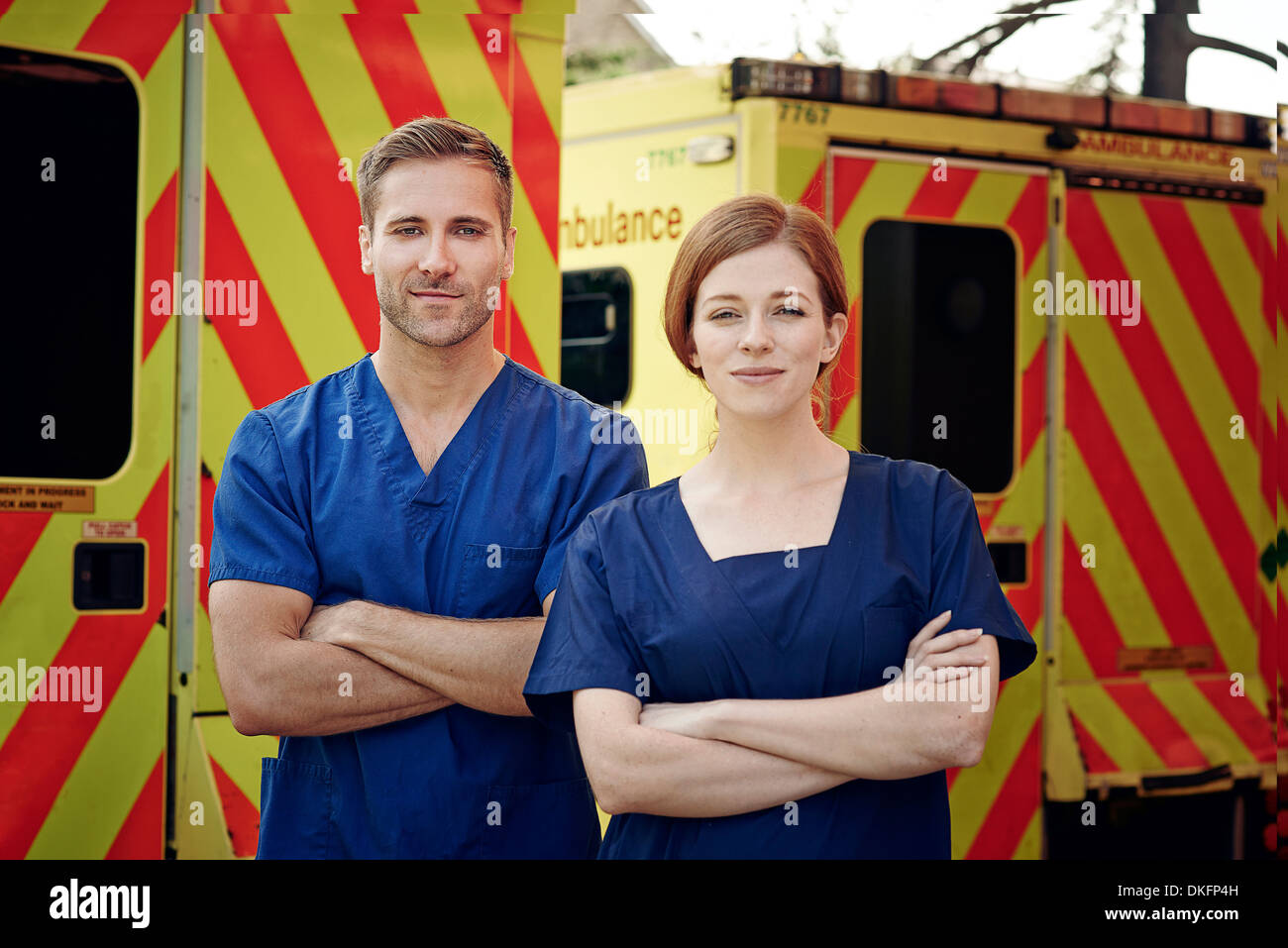 Portrait of two emergency medical technicians next to ambulance - Stock Image
