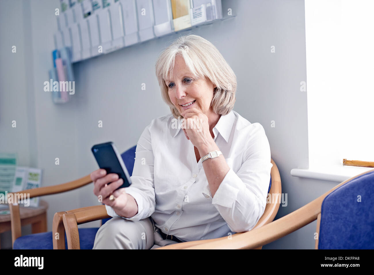 Mature female patient looking at mobile phone in hospital waiting room - Stock Image
