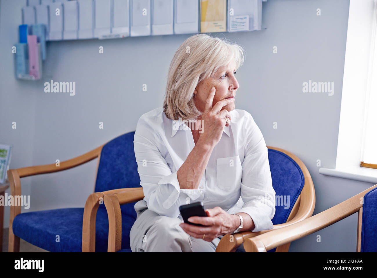 Mature female patient with mobile phone in hospital waiting room - Stock Image