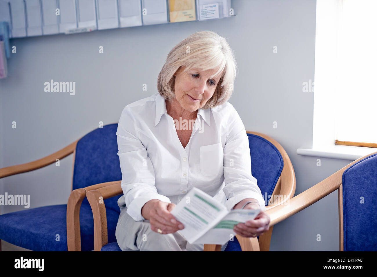 Mature female patient reading leaflet in hospital waiting room - Stock Image