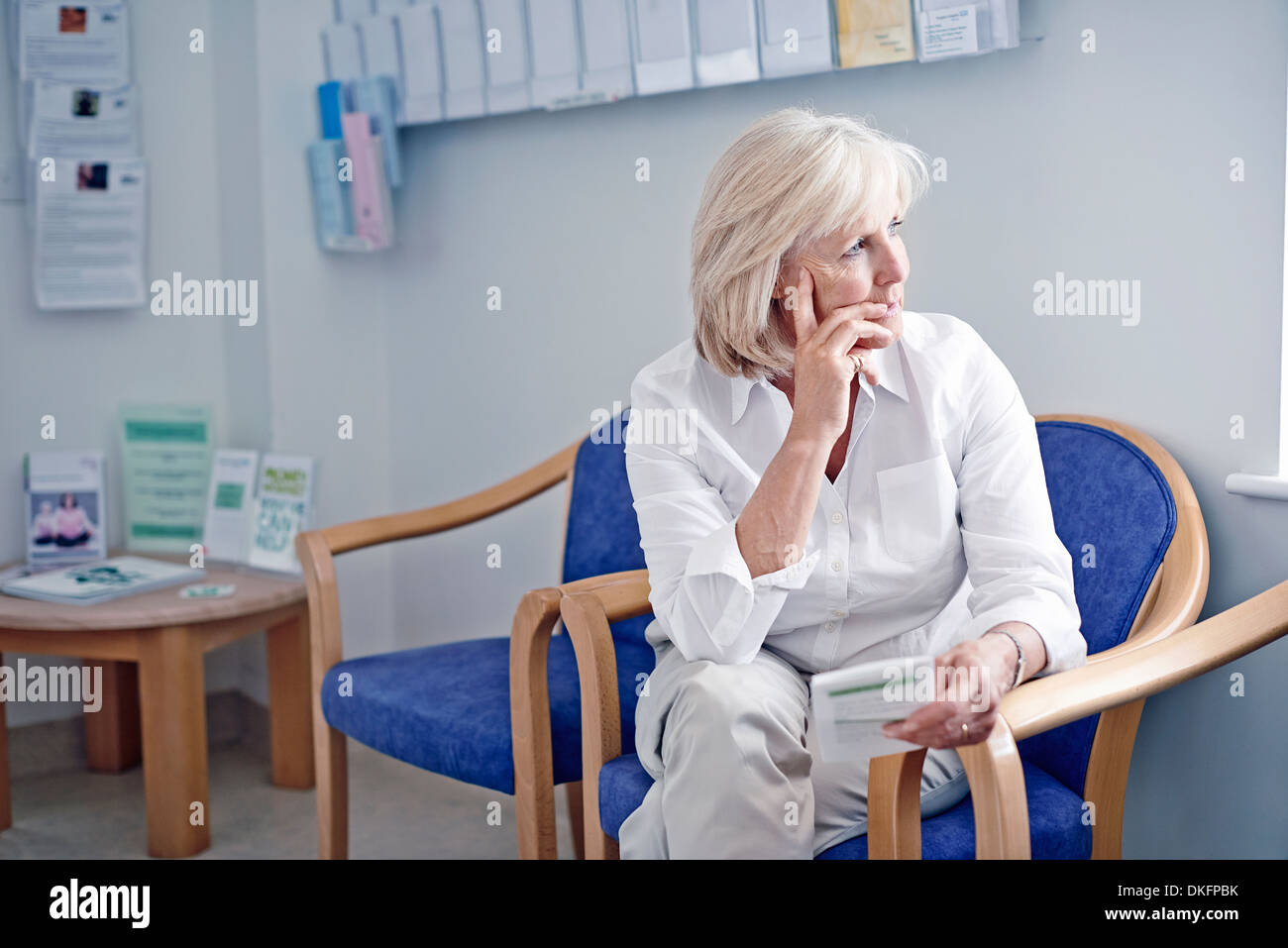 Mature female patient in hospital waiting room - Stock Image