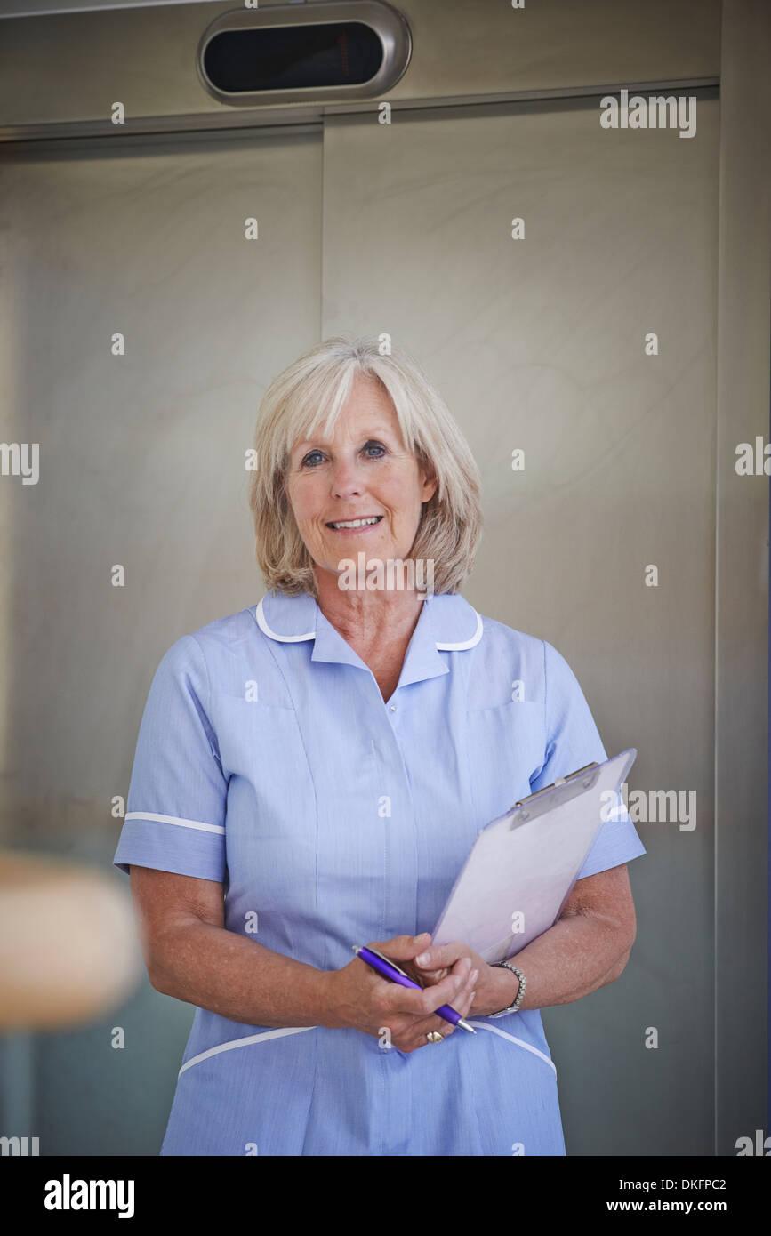 Portrait of mature female nurse in hospital corridor - Stock Image
