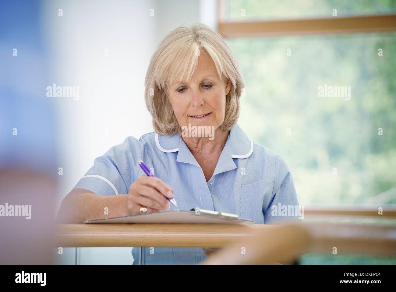 Mature female nurse in hospital corridor with clipboard - Stock Image