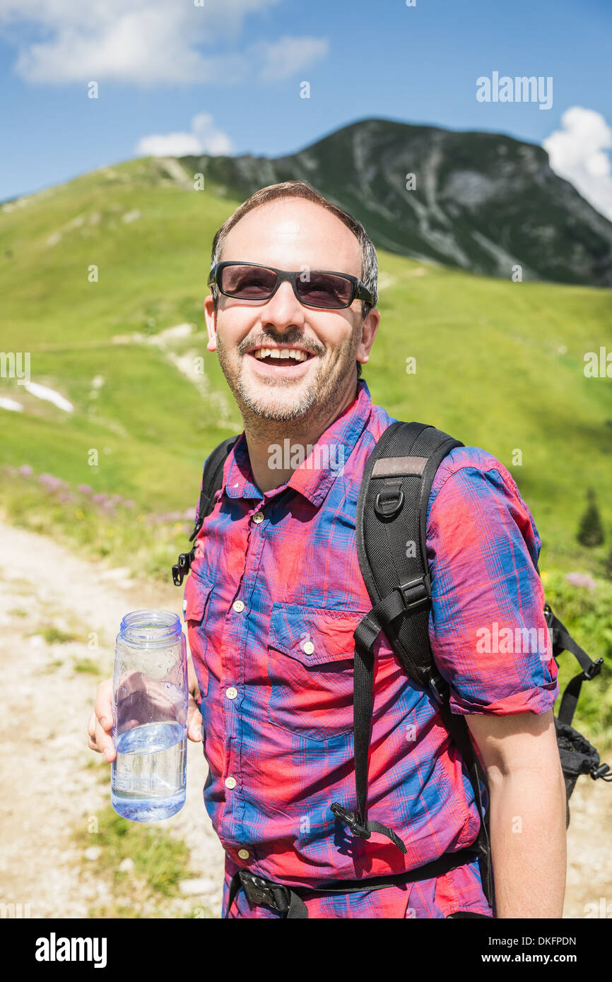 Mature male hiker with bottled water, Tyrol, Austria - Stock Image