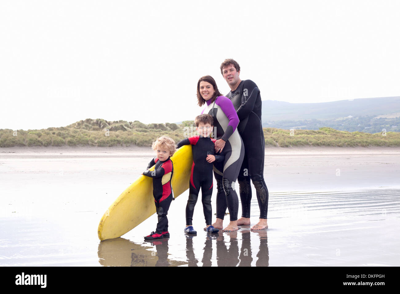 Family with two boys and surfboard on beach - Stock Image
