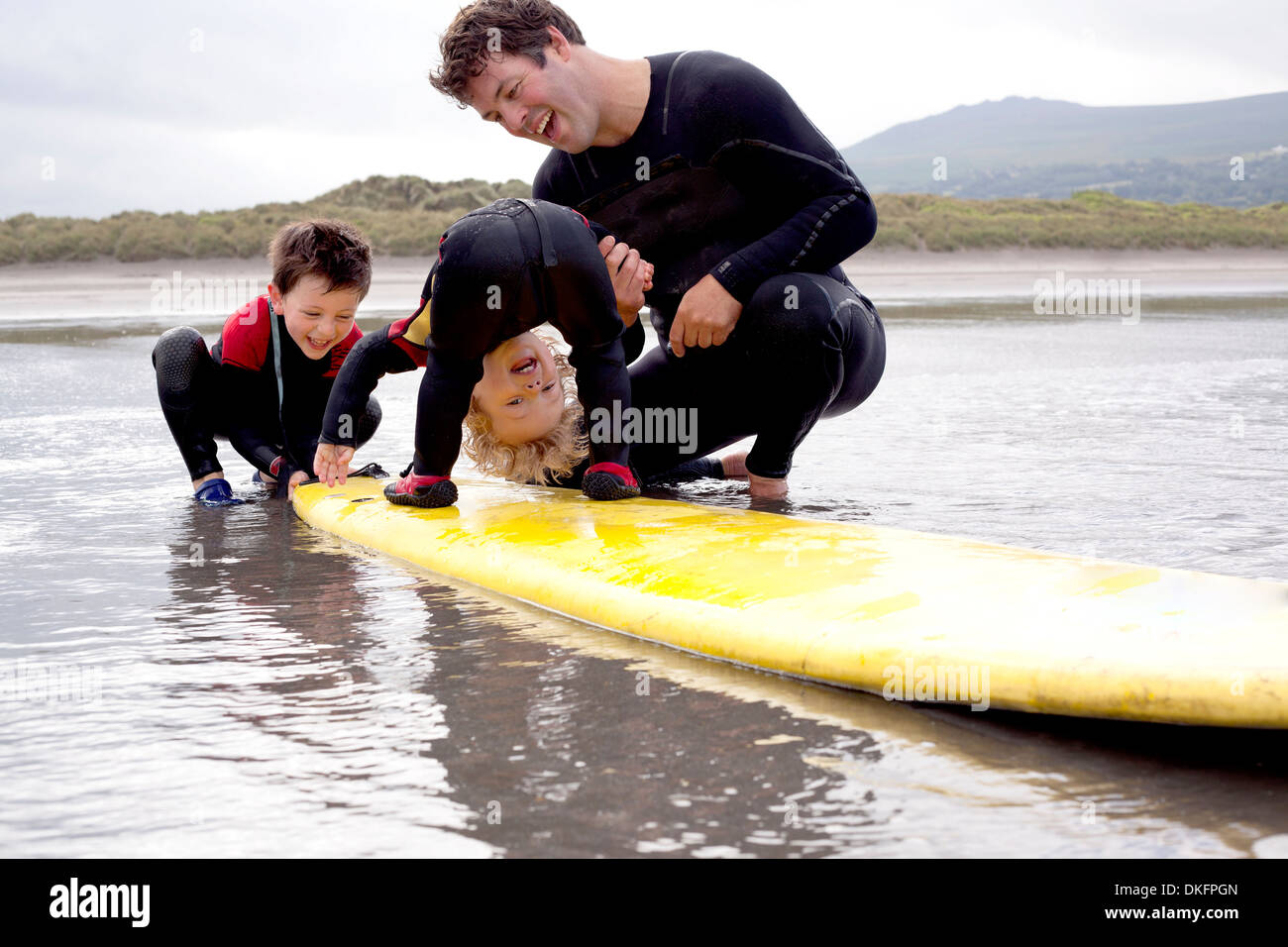 Father and sons playing with surfboard - Stock Image