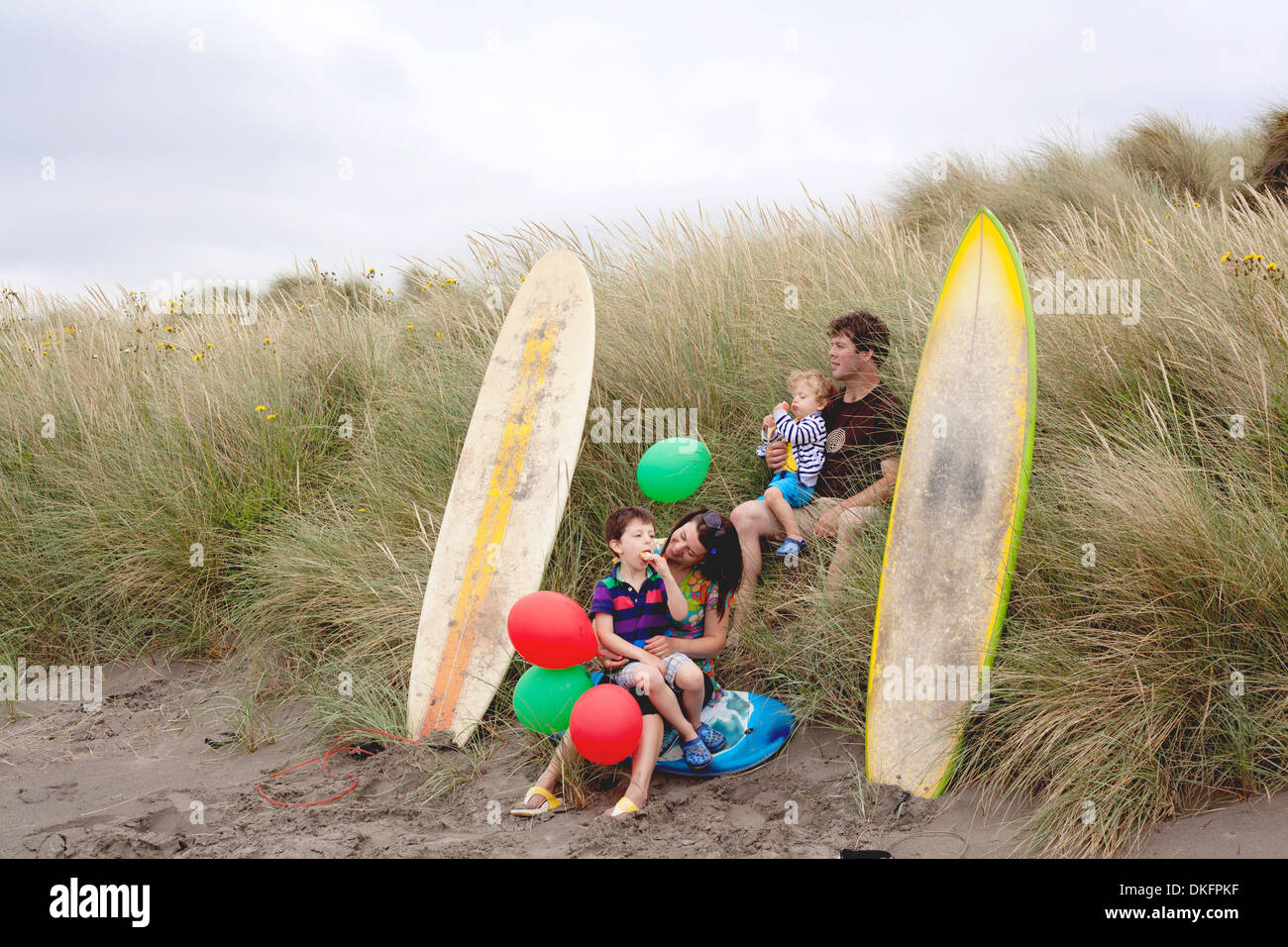 Family with two boys on beach with surfboards - Stock Image