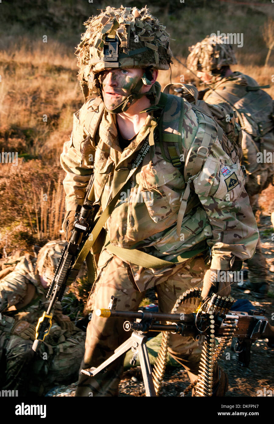 A soldier from 3 Rifles on exercise carrying his personnel weapon (SA80) as well as a GPMG both weapons fitted for firing blanks - Stock Image