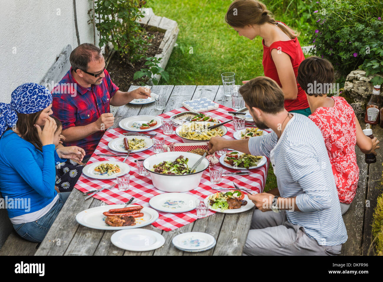 Friends sitting down to picnic lunch, Tyrol, Austria - Stock Image
