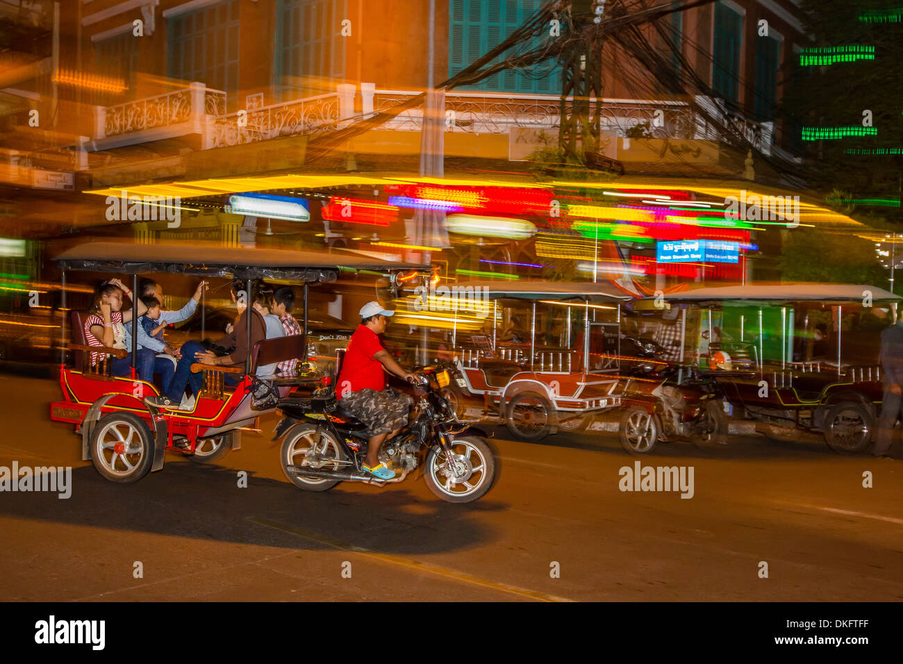 Motion blur image of a tuk-tuk at night in the capital city of Phnom Penh, Cambodia, Indochina, Southeast Asia, Asia - Stock Image