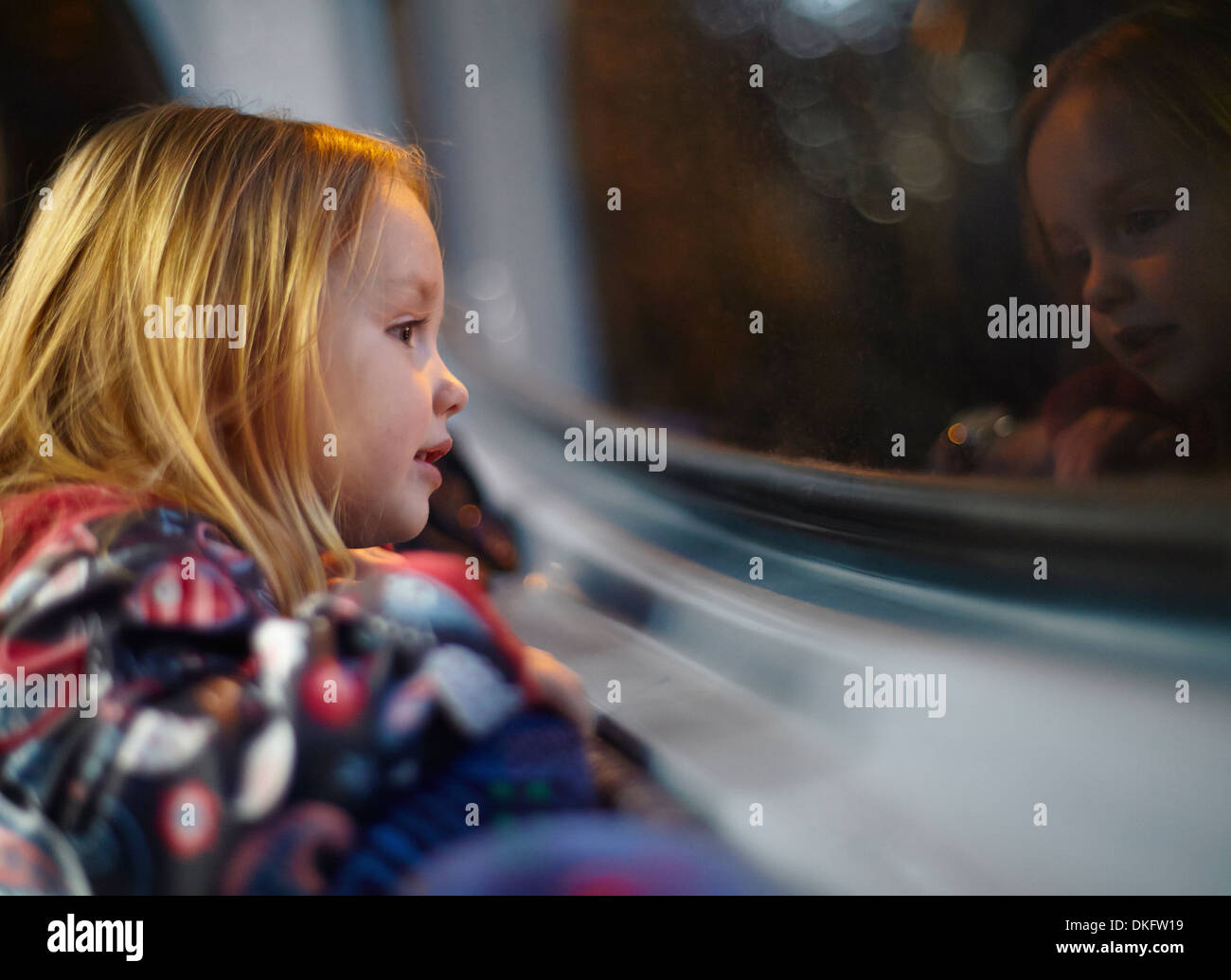 Girl looking out of a bus window during a journey at night - Stock Image