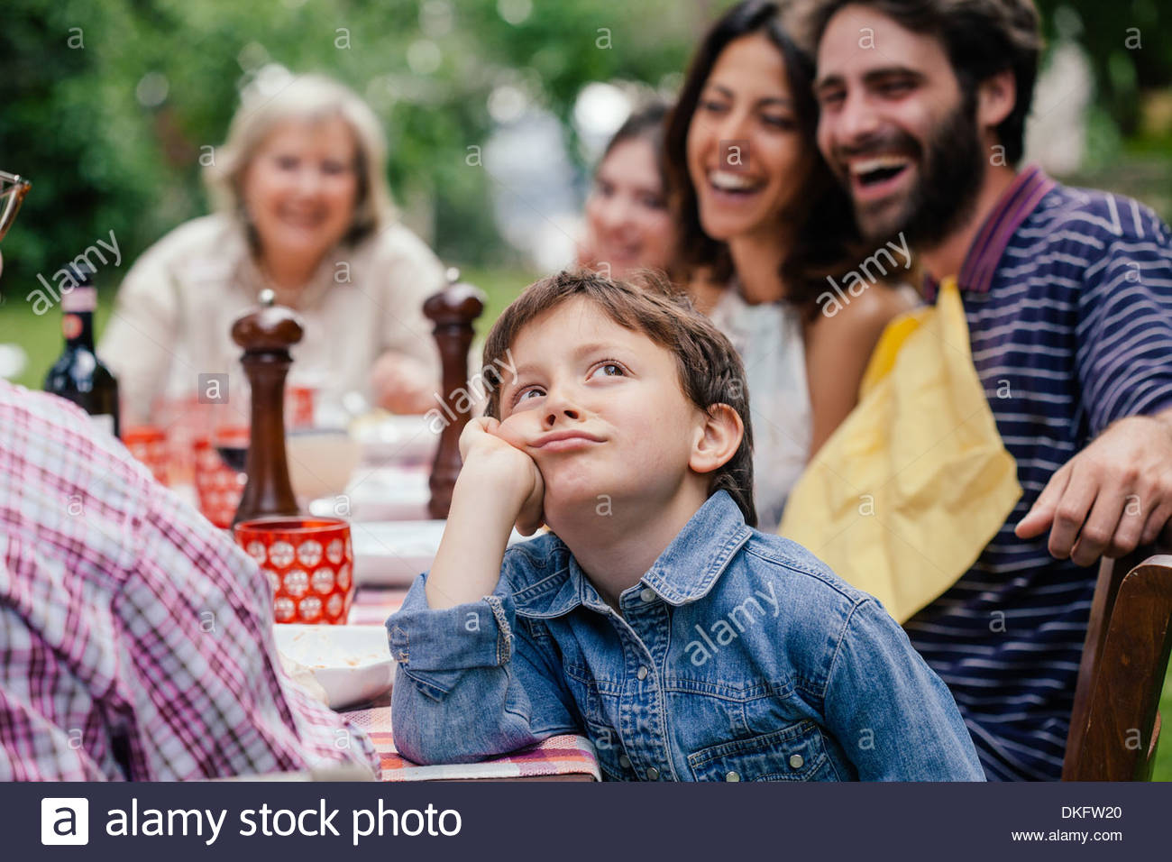 Bored boy at outdoor family meal - Stock Image