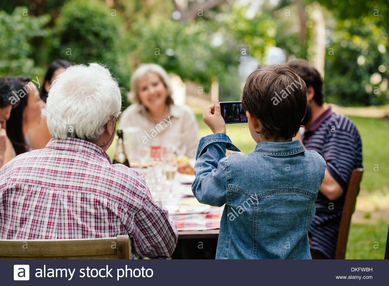 Boy photographing family at outdoor meal - Stock Image