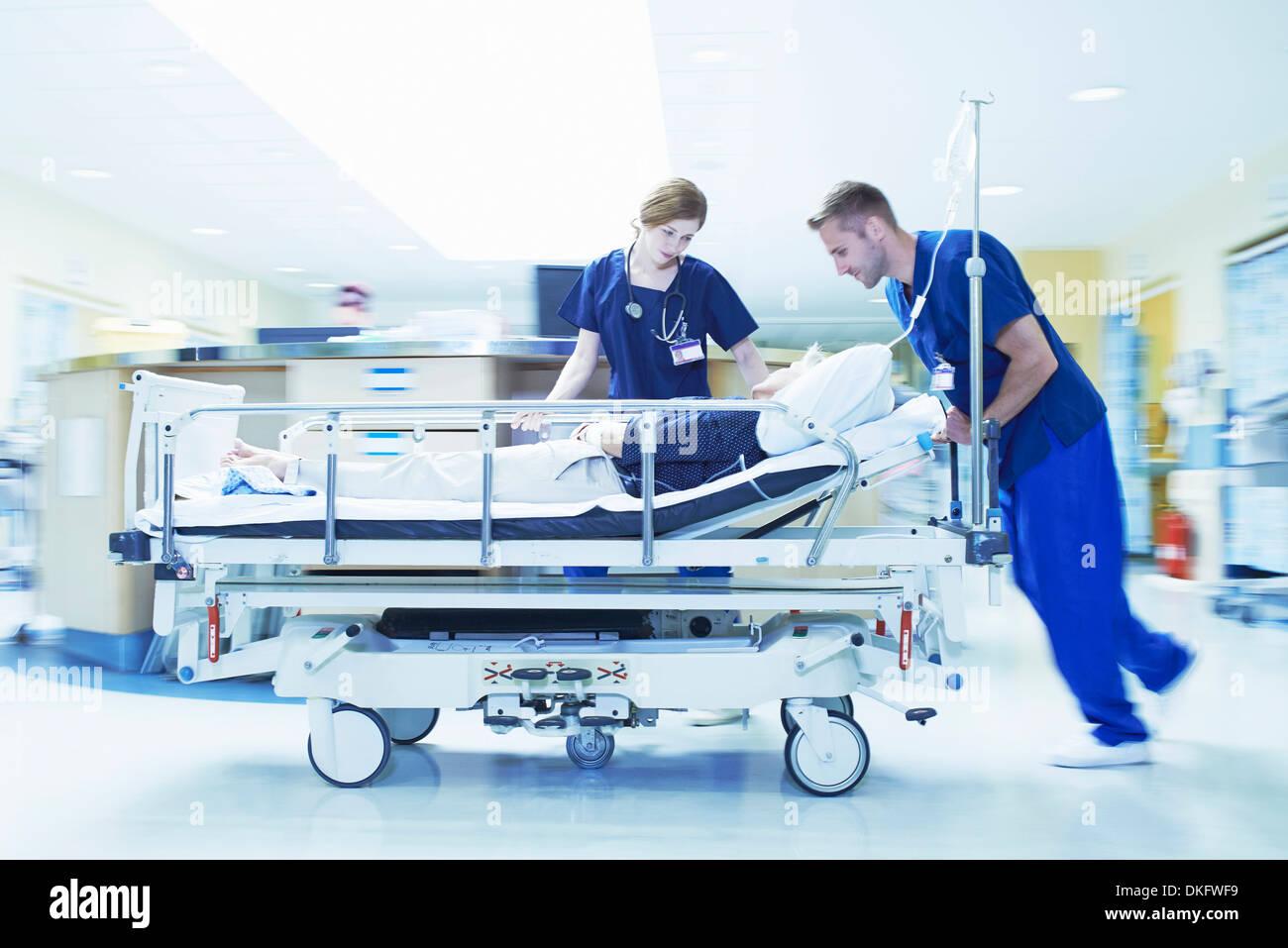 Two medics pushing gurney in hospital emergency room - Stock Image