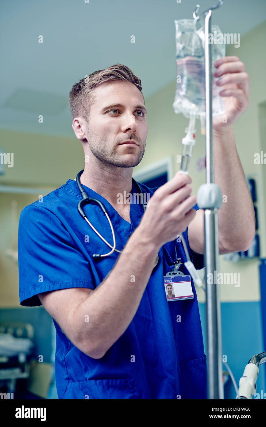 Doctor adjusting intravenous drip in hospital - Stock Image