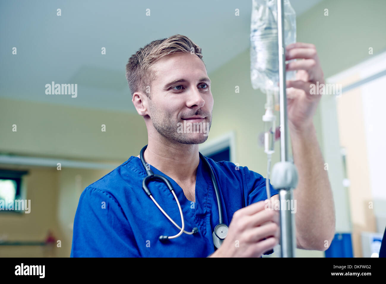 Doctor checking intravenous drip in hospital - Stock Image
