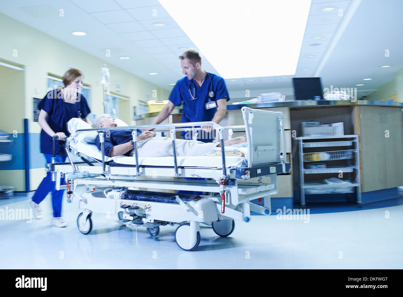 Two medics rushing with gurney in hospital emergency room - Stock Image
