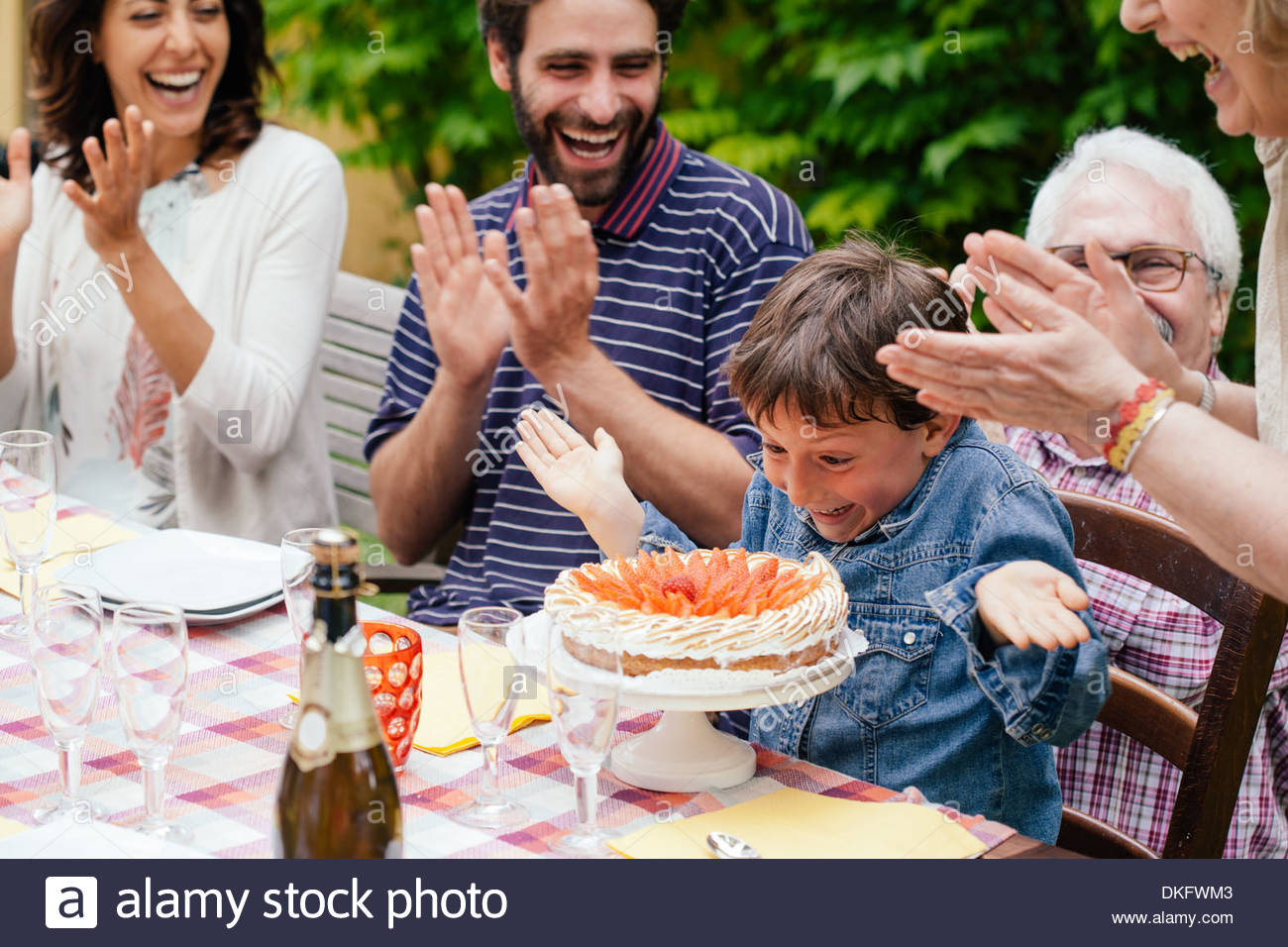 Boy being surprised with birthday cake Stock Photo