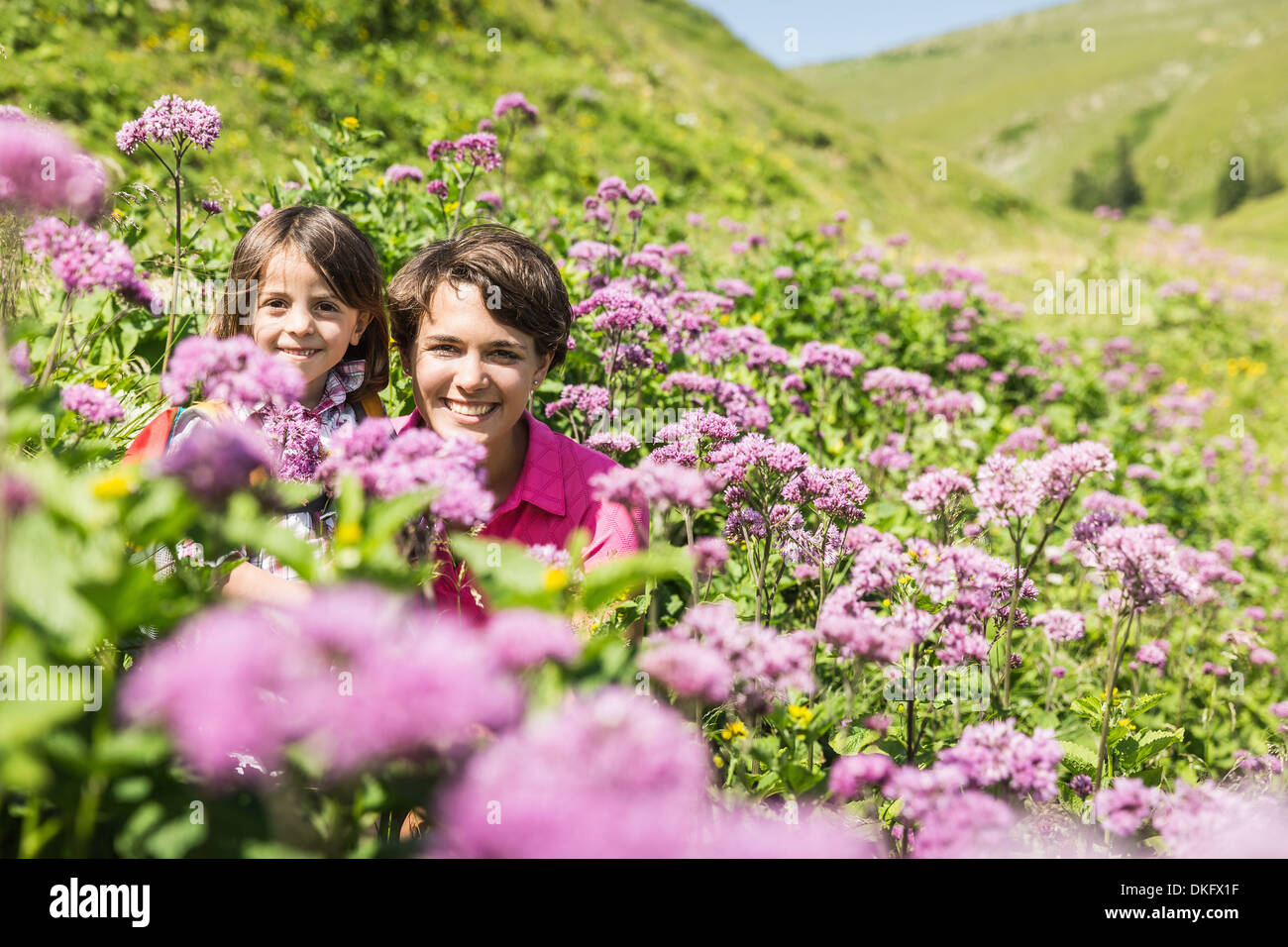 Mother and daughter hiding among wild flowers, Tyrol, Austria - Stock Image