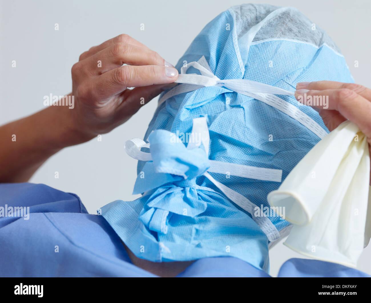 Surgeon putting on surgical mask - Stock Image