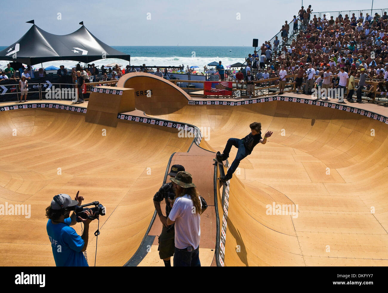 Jul 26, 2009 - Huntington Beach, CA, USA - KEVIN KOWALSKI, right, grinds the coping while practicing for his final heat as Fuel's JEFF KING, center-right, interviews event announcer RYAN CLEMENTS, center-left, during the US Open of Surfing (Credit Image: ZUMApress.com) - Stock Image