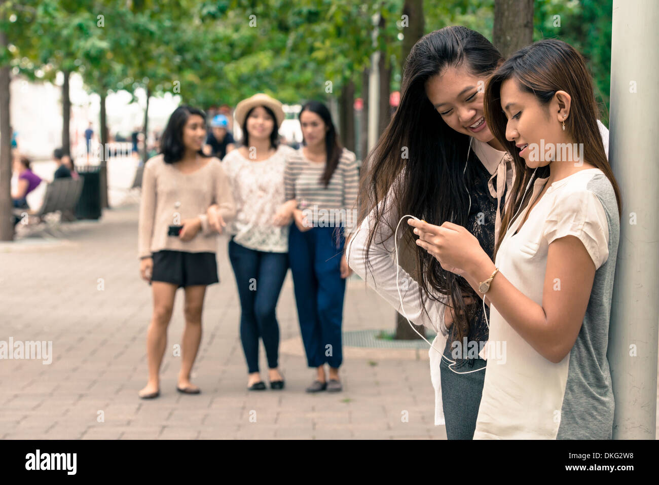 Women looking at technology, friends approaching - Stock Image