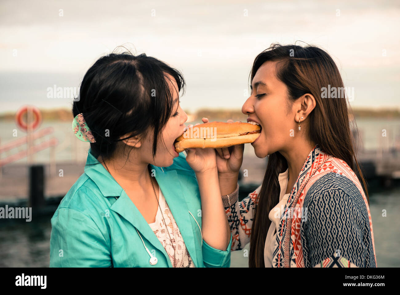 Young women biting opposite ends of sandwich - Stock Image