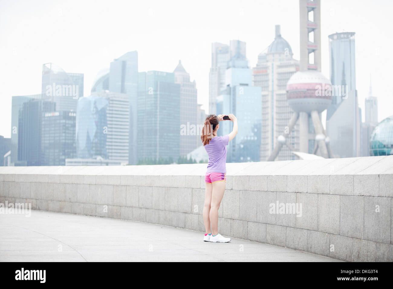 Young woman taking photograph of buildings in Pudong, Shanghai, China - Stock Image