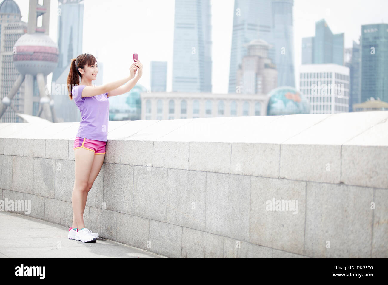Young woman taking photograph in Shanghai, China - Stock Image